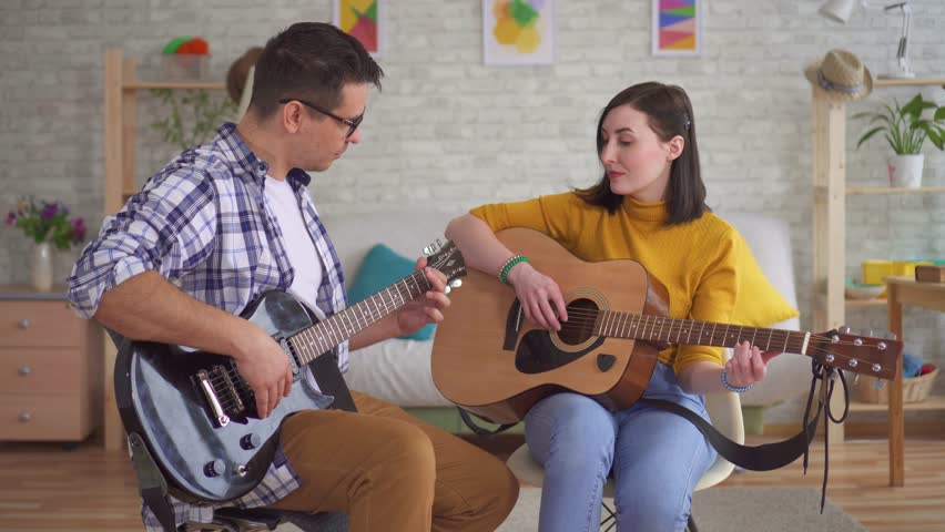 Young man guitarist teaches a young woman to play guitar #1025885651