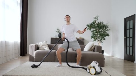 Young Man Having Fun Cleaning House With Vacuum Cleaner Dancing And Using Smartphone.