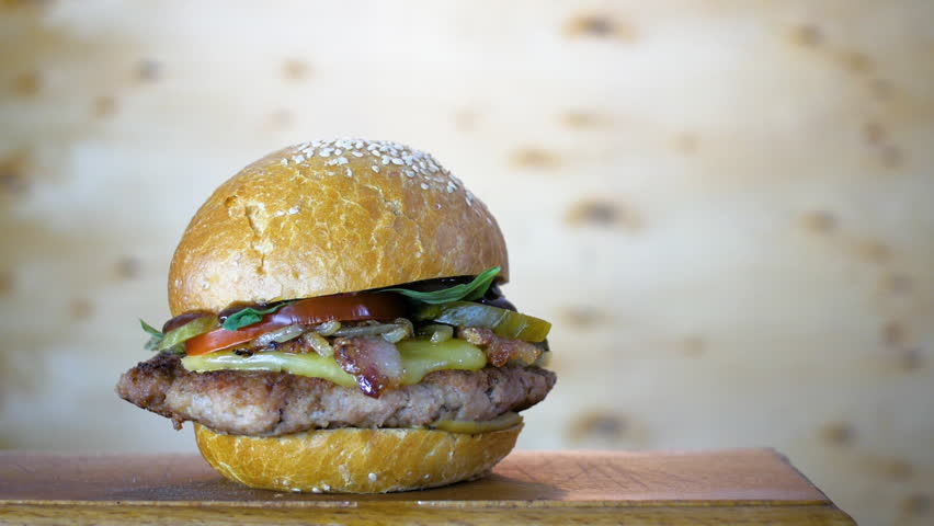 Rotating of fresh-cooked tasty burger on a wooden board, close up | Shutterstock HD Video #1025912381