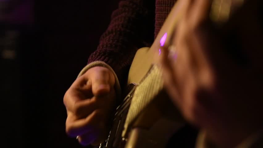 Strumming a guitar chord in slow motion. #1025933111