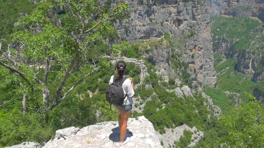 Girl traveler with a backpack goes to the edge on top of a cliff. Woman Healthy Asset. Lifestyle | Shutterstock HD Video #1025967611