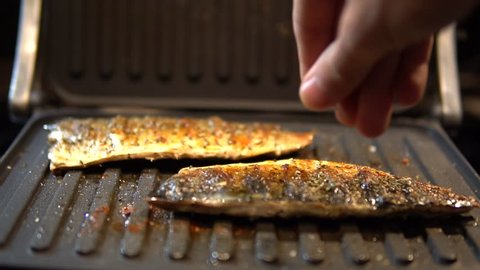 Chef Seasoning Spice Mackerel Fish.Slow Motion Seasoning Fried Fish On Barbecue.Man Sprinkling Spices Over Fried Fish Fillet On Barbecue.Fried Scomber With Spices.Fish Lying On Grill Barbecue.