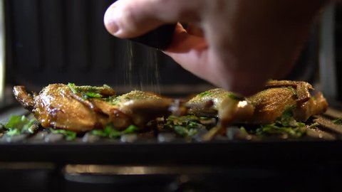 Chef Seasoning Spice Quail Fried On Grill.Quail Fried On Grill.Chicken On Grill.Chicken On Barbecue.Barbeque Chicken On Grill.Pouring Spices On Grilling Quail.Chicken On BBQ Is Seasoned.
