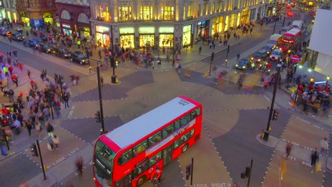 Time lapse of Oxford circus and regent street junction with rush hour traffic of both pedestrians, cars and Red double deck buses.