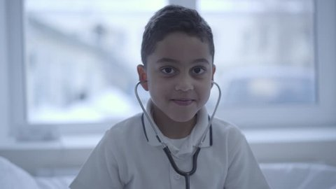 Portrait of cute small boy with stethoscope in his ears looking in camera smiling. Healthcare, healthy lifestyle and medical service concept