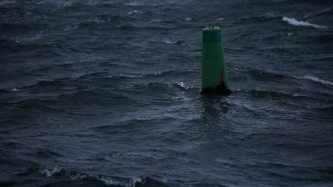 Floating green buoy on vawy waters during storm over Trondheimsfjorden fiord in Trondheim, middle Norway.