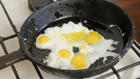 Small quail eggs break into a pan for fried scrambled eggs