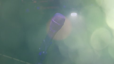 Microphone on the Stand is Standing on the Stage, Close-Up Microphone on the Background of the Auditorium, Spotlight, Backlight. Music instrument concept. Bokeh light effects.