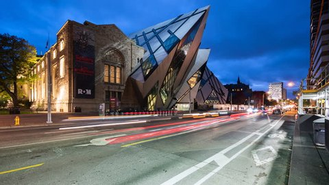 Toronto, Canada - October 24, 2018: Time lapse view of traffic in front of the Royal Ontario Museum aka ROM, the largest and most-visited museum in Canada, at dusk in Toronto, Ontario, Canada.