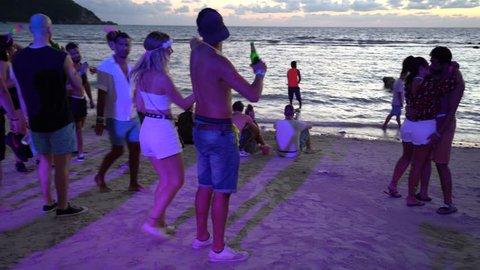 KOH PHANGAN, THAILAND - FEBRUARY 21, 2019 : Girls and guys participate in Full Moon party in island Koh Phangan, Thailand. Crowds of people dance on the sandy beach during the full moon party