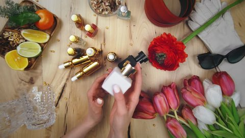 Perfumer demonstrating her fragrance. Top view of bottles of perfume on table surrounded by female accessories and flowers