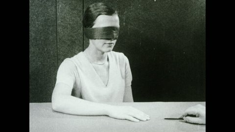 1930s: Blindfolded woman sits at table. Hand uses sharpened pointer to prick woman's hand. Woman jerks hand away.