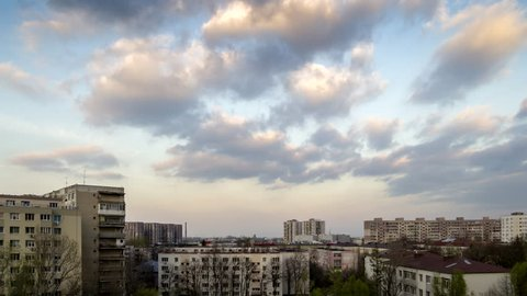 Urban time lapse: Contrast between pink cumulus clouds on blue sky at evening and old, communist era buildings with gray and poorly maintained exteriors, in Bucharest, Romania. 4K with ProRes codec.