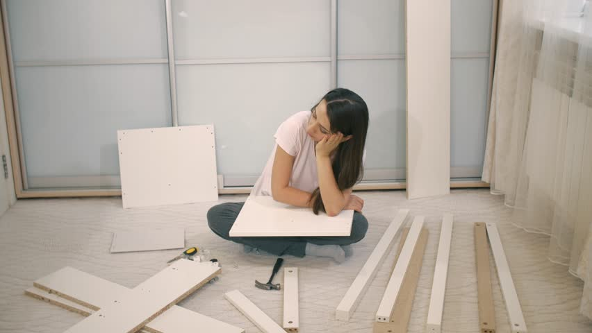Sad woman can't to assemble furniture | Shutterstock HD Video #1026185291