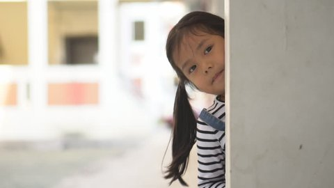 Asian child cute or kid girl playing peekaboo or hide and seek with sneaked or dodge behind the post and happy smiling white teeth or cheerful at public park or playground on relax holiday on slow