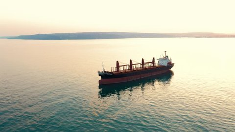Aerial view of a large high-speed sea vessel for transportation of a dry-cargo ship with a closed hold is anchored near the seaport city and awaits unloading. Import and export by sea. Smooth water
