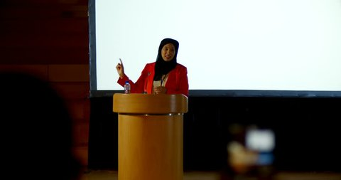Front view of beautiful mature Caucasian hijab businesswoman speaking at podium in auditorium. She is gesturing and clasped hands.