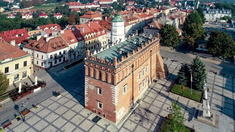 Sandomierz old city, Poland.. Market square, Gothic city hall with clock tower and Renaissance attic and St Mary statue . One of the oldest towns in Poland. Aerial 4K revealing video in sunrise light