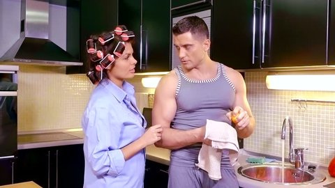 Husband and wife in the kitchen . man wash citrus fruit and wipe with a towel. woman with curlers in her hair talking with a man