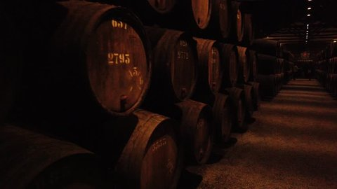PORTO, PORTUGAL - CIRCA MARCH 2019: Port wine cellar, wooden barrels. Tawny port wine is aged in wooden barrels, stored in a cave before being bottled.