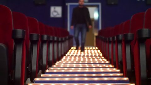 A blurred man walks down the center aisle of an emptyie theatere in slow motion