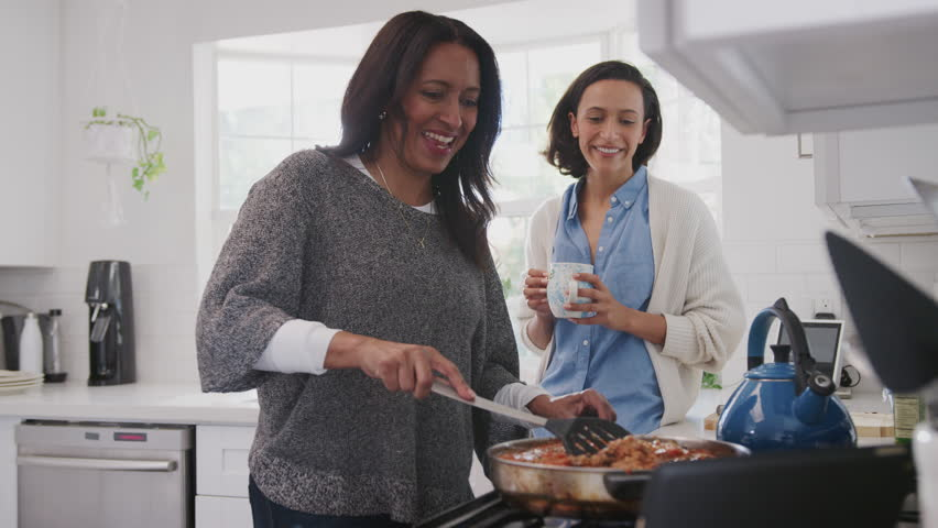 Middle aged woman standing in the kitchen cooking, her adult daughter standing beside her talking | Shutterstock HD Video #1026410111