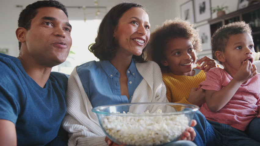 Young mixed race family sitting on the sofa watching TV and eating popcorn, low angle, close up