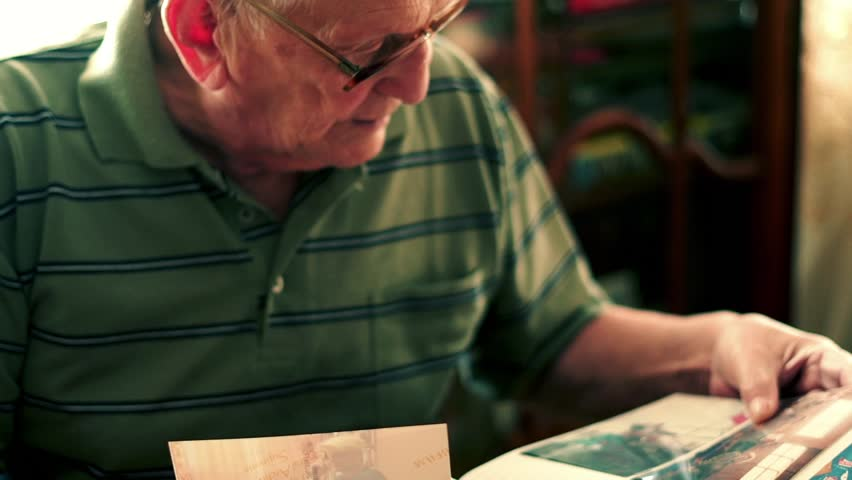 Senior man looking at photos by table at home, 4K  | Shutterstock HD Video #1026448331
