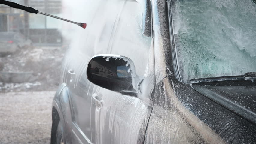 Slow Motion Video of a Car Washing Process on a Self-Service Car Wash. A Jet of Water With a High Pressure Wash Off the Dirt From the Car. Side View. Foamed Detergent Drains From the Car Windows and | Shutterstock HD Video #1026451241