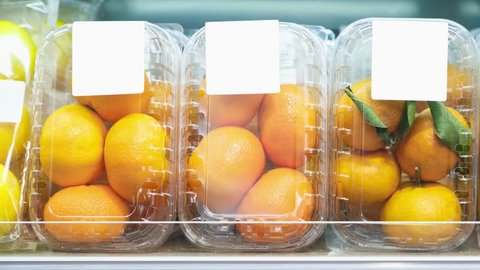 Footage of plastic containers with ripe orange fruits in food aisle at supermarket.Buy natural fruit for healthy nutrition.Oranges packed in transparent boxes in market