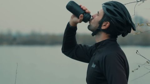 Cyclist Drinking Water From Water Bottle.Man In A Helmet With A Bicycle Drinks Water.Close-Up Slow Motion Cyclist Drinking.Athlete Cyclist Man Drinking Water During Cycling Biking Training.Biker Drink