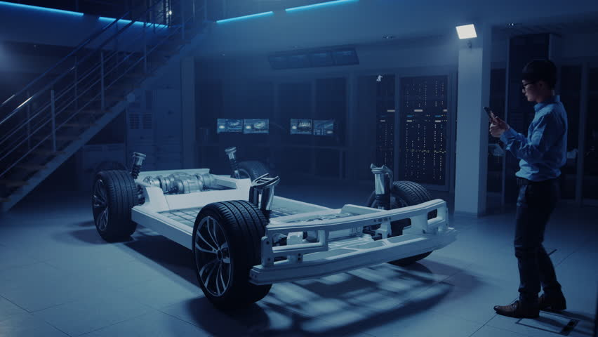 Automobile Engineers Working on Electric Car Chassis Platform, Using Tablet Computer Augmented Reality with CAD Software for 3D Concept. In Automotive Innovation Facility Vehicle Frame with Wheels | Shutterstock HD Video #1026560951