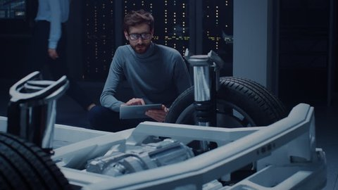 Automobile Design Engineer Sitting Beside Hybrid Electric Car Chassis Platform Prototype, Using Tablet Computer for Design Enhancement. Facility with Vehicle Frame with Suspension, Wheels, Engine