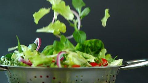 Fresh salad flying to colander in super slow motion.