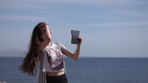 Girl makes selfie with her phone in slow motion on the beach.