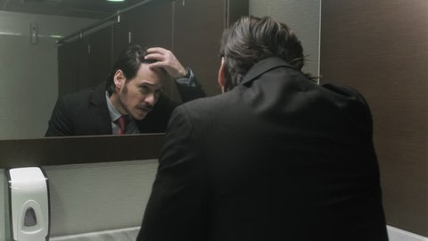 Business man in office bathroom. Stressed manager using restrooms, washroom and lavatories while looking at receding hairline. Male beauty in public toilet with businessman checking hair for loss