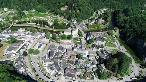 Aerial 4K, drone flying around old town and Castle in Durbuy, Belgium, surrounded by mountains, river and kayakers on the river in green kayaks paddling in a beautiful green scenery in summertime