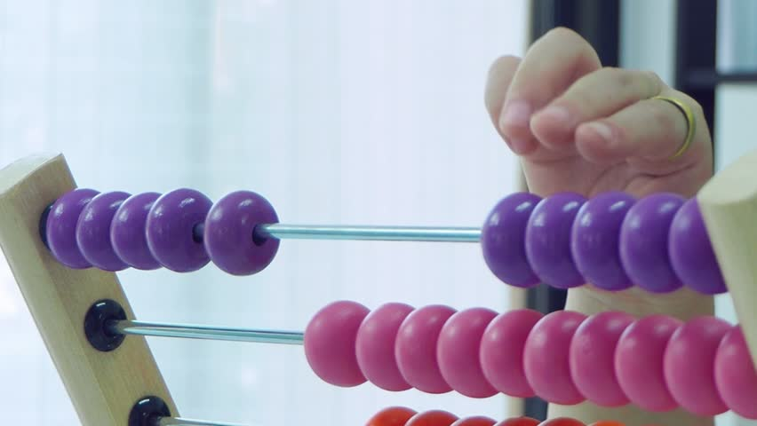 Hand of a girl playing with colorful wooden abacus  | Shutterstock HD Video #1026767081