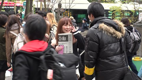 "SHIBUYA,  TOKYO,  JAPAN - CIRCA APRIL 1st 2019 : ""REIWA"" becomes the new name, for a new era, under a new Emperor.  People holding copy of Asahi newspaper reporting the name of new era."