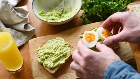 Toast with mashed avocado and boiled egg. Man preparing tasty breakfast toasts