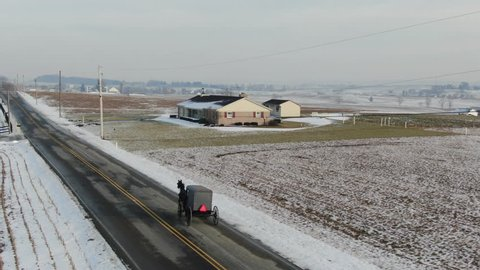 Amish buggy with horse driving over empty road in rural area. Shot in Intercourse, PA in winter. A beautiful snow covered rural town with farms, meadows, farmlands and a small village center.