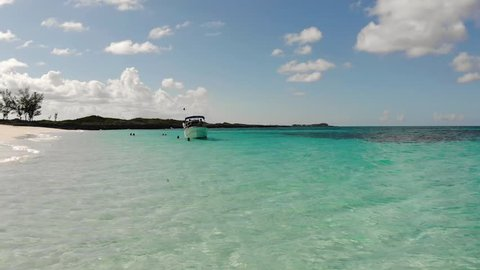 Aerial - fishing boat waits whilst people snorkel in the perfectly blue waters of the Bahamas, Rose Island, Caribbean, Coral Reef and beautiful beach