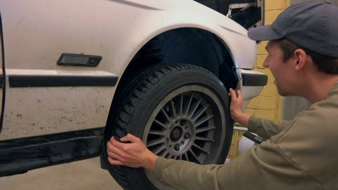 Mechanic doing inspection and service on car in garage. Checking suspension, shock absorber and wheel bearings.