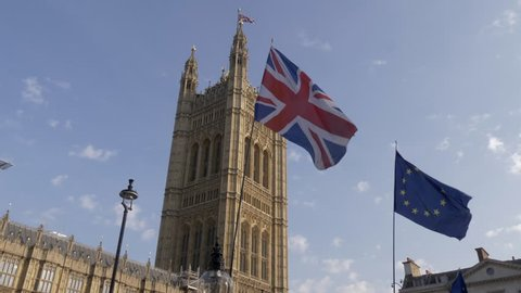 European and British flags in front of House of Parliament, London.