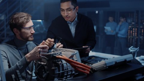 Two Professional Automotive Engineers with a Tablet Computer and Inspection Tools are Having a Conversation While Testing an Electric Engine in a High Tech Laboratory with a Concept Car Chassis.