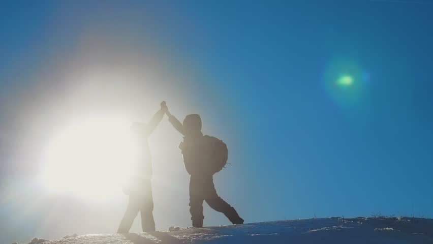 teamwork winners tourists winter snow business travel trip met on top of a mountain. two men with backpacks hiking met in the silhouette in mountains with sunlight. slow motion video. rock climbers