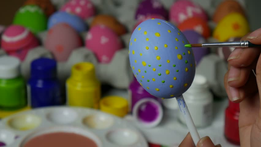 Coloring eggs with various colors beautifully with the brush during the Easter. Woman paint on easter eggs. Beautiful art on eggs in easter festival. | Shutterstock HD Video #1026864341