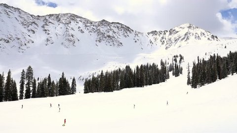 People skiing and snowboarding in the winter snow of the Rocky Mountains at Arapahoe Basin in Colorado