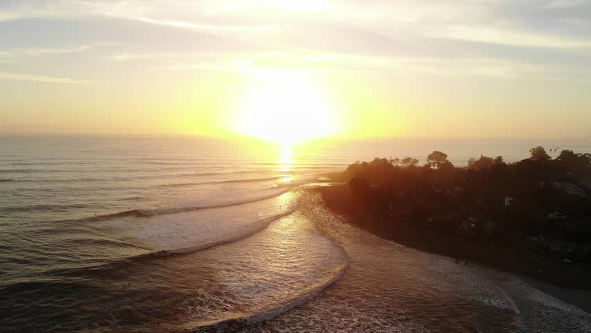 Aerial drone at Rincon Point beach surf break with ocean waves and people surfing at sunset on the beautiful California coastline.   Shutterstock HD Video #1026884921