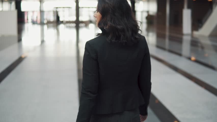 A business woman exits through the revolving doors of a modern business center. girl in a business suit looks at watch. back view | Shutterstock HD Video #1026936671